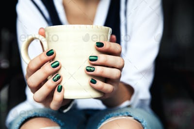 Stylish fashionable girl with a Cup of coffee and a green manicure in jeans. Fashion, care, beauty