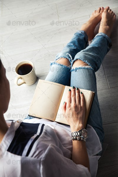Young modern girl in torn jeans reading a book with a big cup of coffee. lifestyle, education