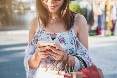 Young woman using smartphone with shopping bags at shopping mall