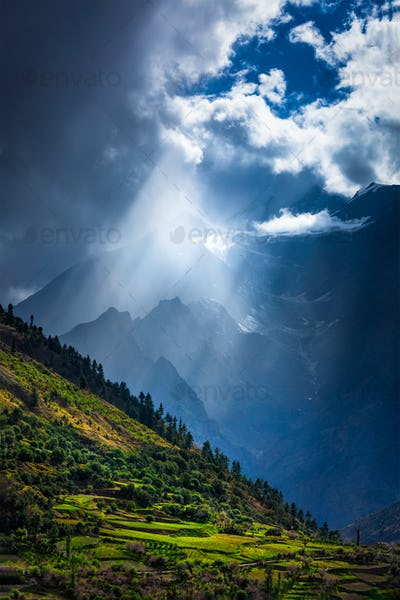 Sun rays through clouds in Himalayan valley in Himalayas