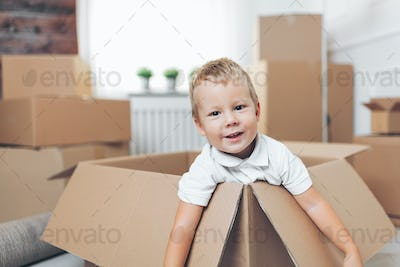 Cute toddler helping out packing boxes