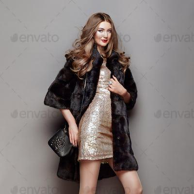 Fashion portrait young woman in black fur coat