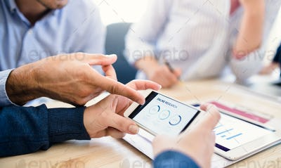 Group of businesspeople with smartphone working together in office, midsection.