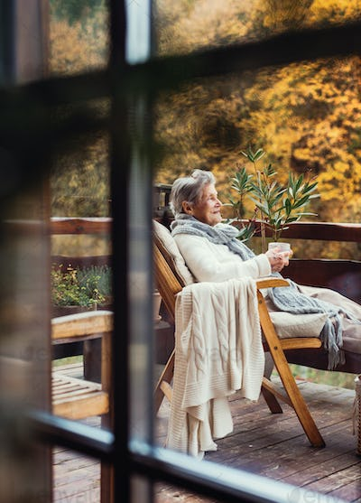 An elderly woman sitting outdoors on a terrace in on a sunny day in autumn.