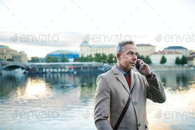 Mature businessman with smartphone standing by river Vltava in Prague city.