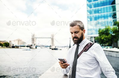 Hipster businessman with smartphone standing by the river in London, texting.