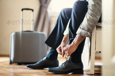 Midsection of businessman on a business trip sitting in a hotel room, tying shoelaces.