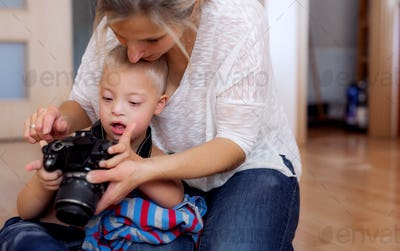 A down syndrome boy and his mother with a digital camera indoors.