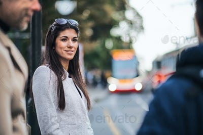 Attractive woman standing outdoors in city, waiting for a tram.