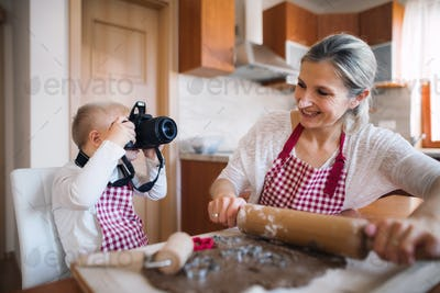 A down syndrome boy with a camera and his mother indoors baking.