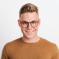 A confident young man in a studio, wearing glasses.