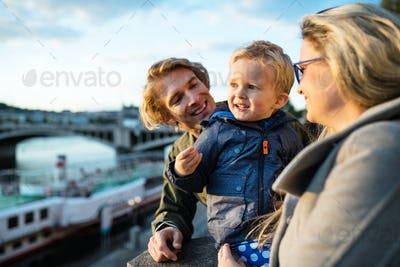 Young parents with their toddler son standing outdoors by the river in city.