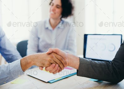 Handshake of male businesspeople in an office. Midsection.