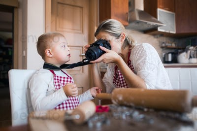 A down syndrome boy and his mother with a camera indoors baking.