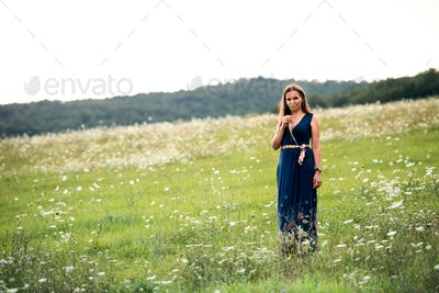 A young woman standing in nature on a summer day, smelling flowers. Copy space.