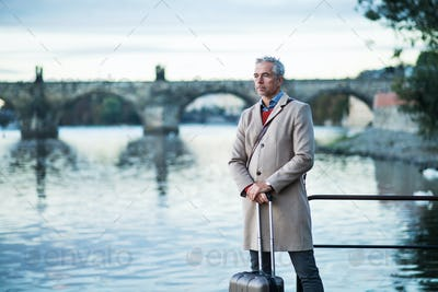 Mature businessman with suitcase standing by river Vltava in Prague city.