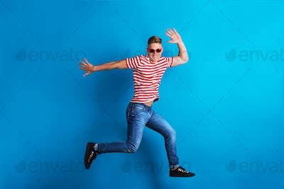 A young man with red sunglasses in a studio, jumping.