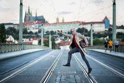 A happy mature businessman with bag crossing a road in Prague city.