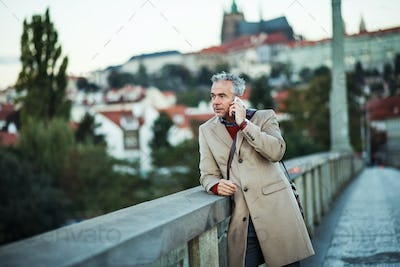 Businessman with smartphone standing on a bridge in city, making a phone call.