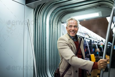 Mature businessman with smartphone travelling by tram in city.