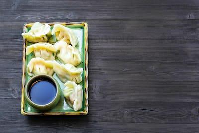 Dumplings on plate on dark table with copyspace