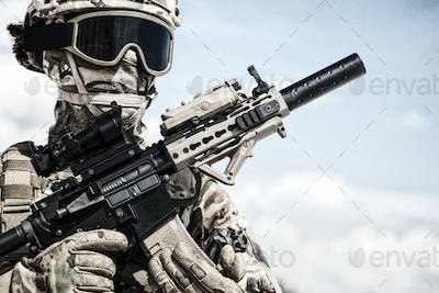 Airsoft player soldier in military ammunition replicas