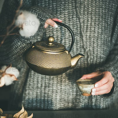 Female pouring tea from golden pot into cup, square crop