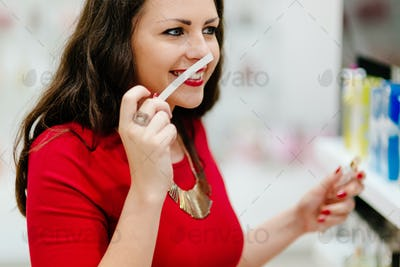 Happy woman testing perfumes in shop