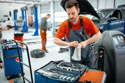 Car mechanic keeping tools polished