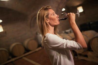 Female tasting wine in winery