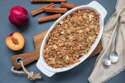 Plum crumble pie or plum crisp with oats and spices, in a baking