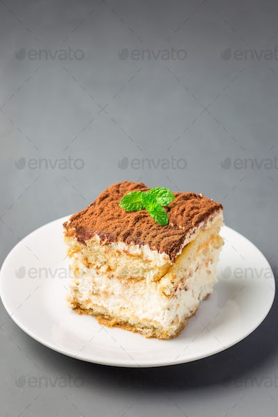 Piece of traditional italian Tiramisu dessert cake on white plat