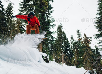 snowboarder in red suit is riding in the mountain forest