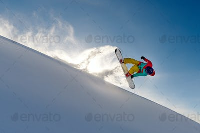 girl snowboarder jumping front flip leaving a wave of snow