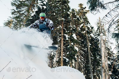 snowboarder with snowboard is jumping very high in the mountain forest