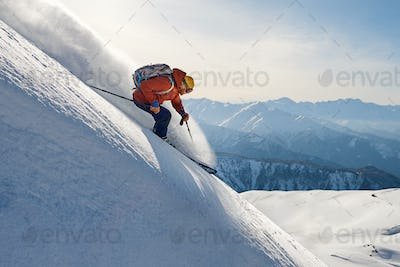 skier rides freeride on powder snow down slope against the backd