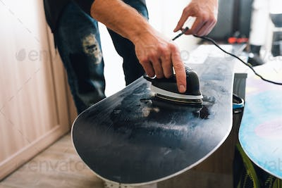 man is waxing a snowboard