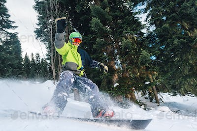 snowboarder with special equipment is riding and slow down in the mountain forest