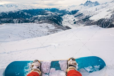 snowboarder with snowboard is sitting on the mountain