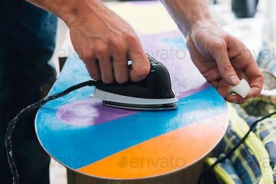 man is waxing a snowboard