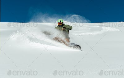 man snowboarder curved and brakes sprinkling snow on   freeride