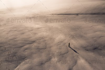 One skier in  snow field at sunset view from above