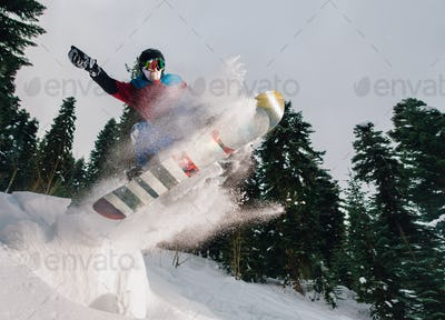 snowboarder is jumping very high and freeriding from hill in the mountain forest