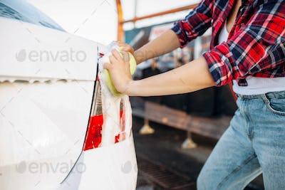 Female person scrubbing vehicle rear lights