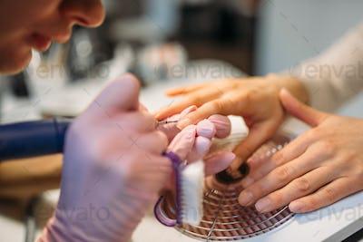 Beautician with polishing machine treats nails