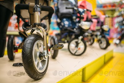 Row of strollers in store with goods for newborns