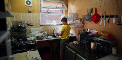 boy washing dishes in the kitchen in a yellow t-shirt