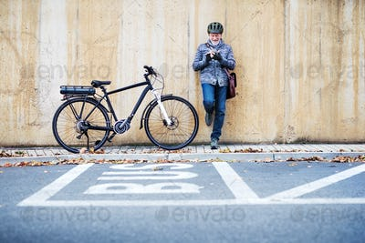 Active senior man with electrobike standing outdoors in town, using smartphone.