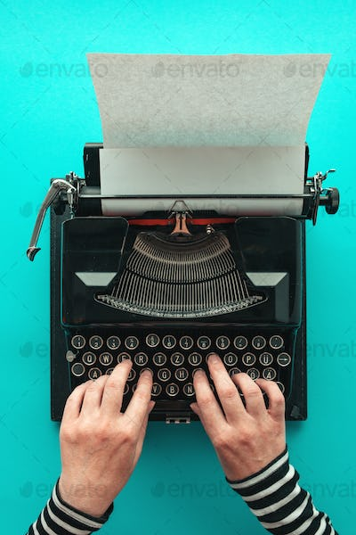 Woman typing vintage typewriter, top view