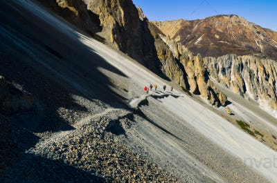Group of mountain trekkers walking on a steep rocky hill in Himalayas, Nepal